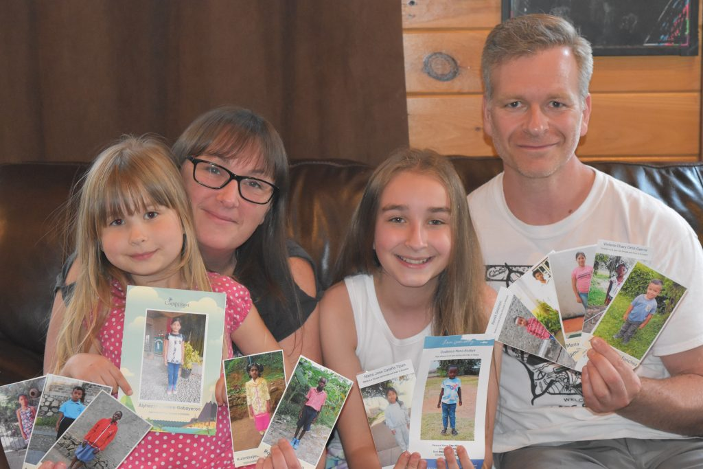 Josh, his wife and his two daughters hold up pictures of their sponsored childen