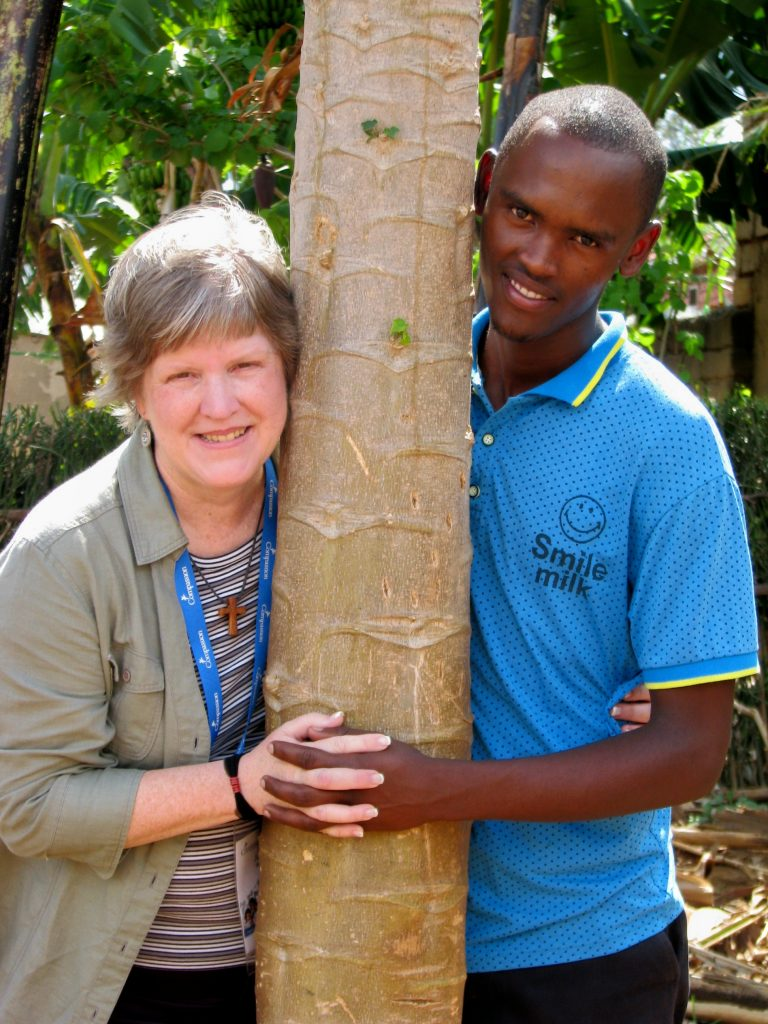 Judy poses around a tree with her sponsor child.