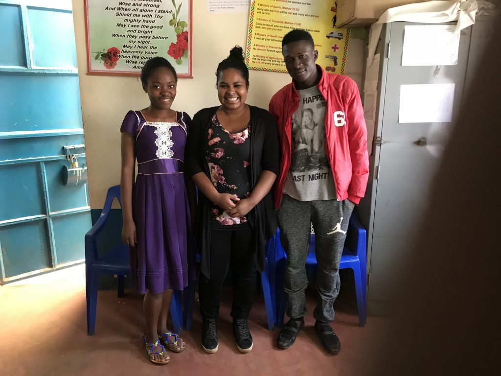 Sarah poses with both of her sponsor children in a classroom.