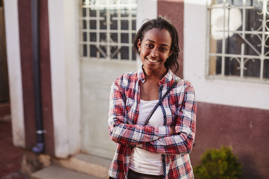 A portrait of Betey. She is wearing a red plaid shirt over a white t-shirt. Her arms are crossed.