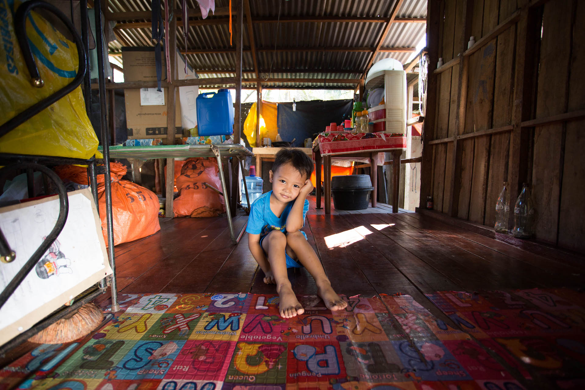 A young Filipino boy sits on the floor of his home. His legs are straight out in front of him and his head leans on his arm. He is wearing a blue t-shirt.