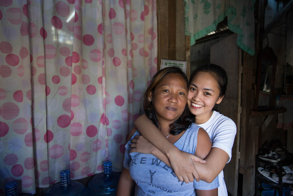 Maricris stands behind her mother with her arms around her. Maricris is wearing a white t-shirt and smiling, her mother is wearing a light purple t-shirt and has a neutral look on her face.