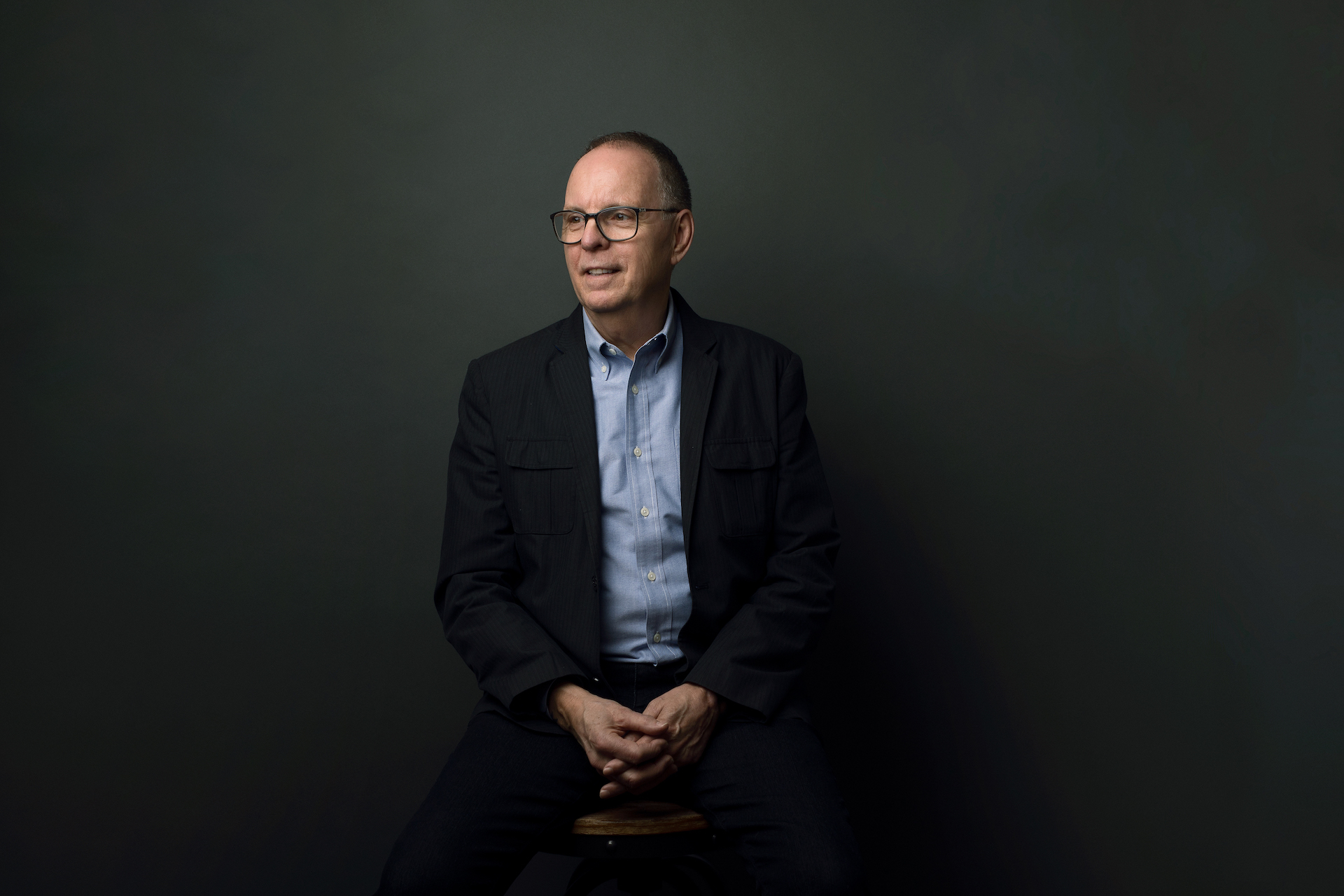 a portrait of Barry. He is wearing a blue shirt and black blazer, sitting and looking into the distance.
