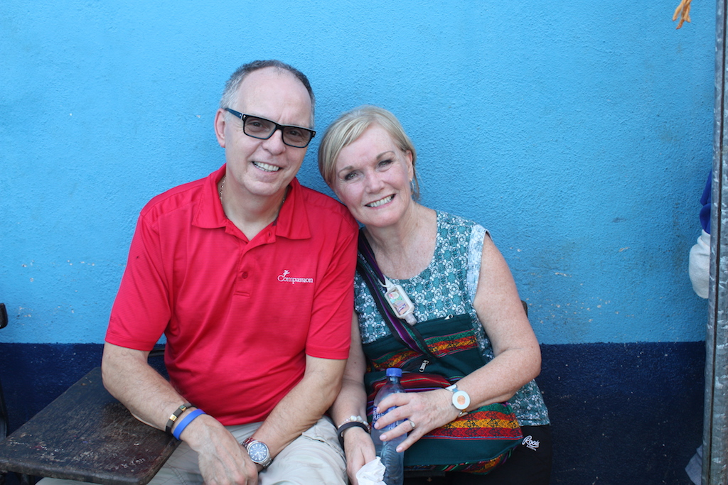 Barry and Sharon together in one of Compassion's field countries. Barry is wearing a read polo shirt and Sharon is wearing a blue patterned top.