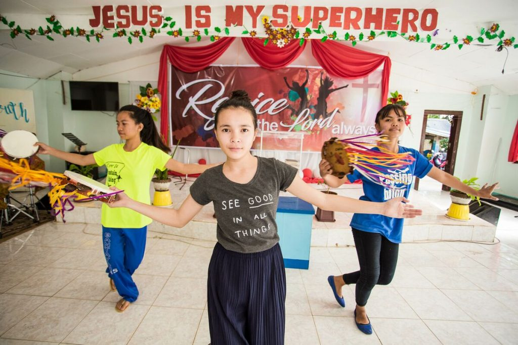 "Bea dances with a group of girls under a banner that says ""Jesus is my superhero"""