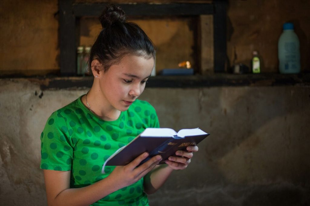 Bea reads her bible in her room wearing a bright green t-shirt.