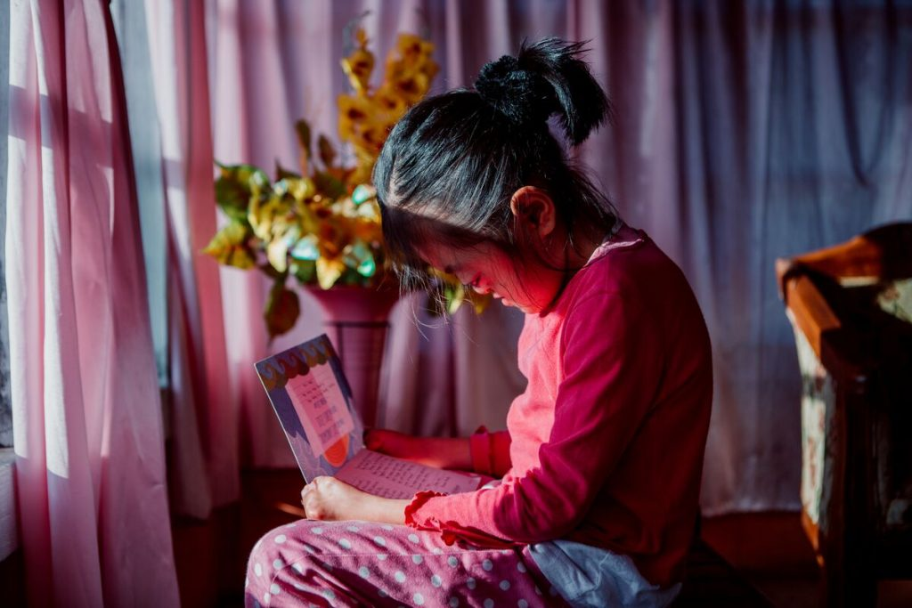 Karunia sits in her room reading a letter. Her windows are surrounded in pink curtains.