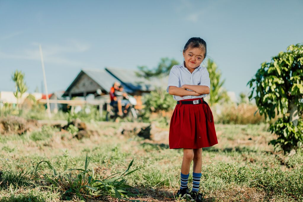 Karunia stands with her school uniform on, crossing her arms and smiling infront of her school.