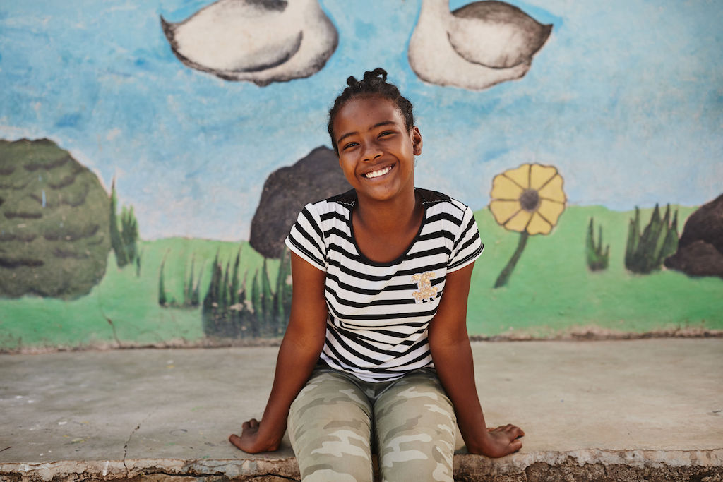 A portrait of Seferash. She is sitting on a step in from of a mural, smiling. She is wearing a black and white stripe tshirt and green camouflage pants.