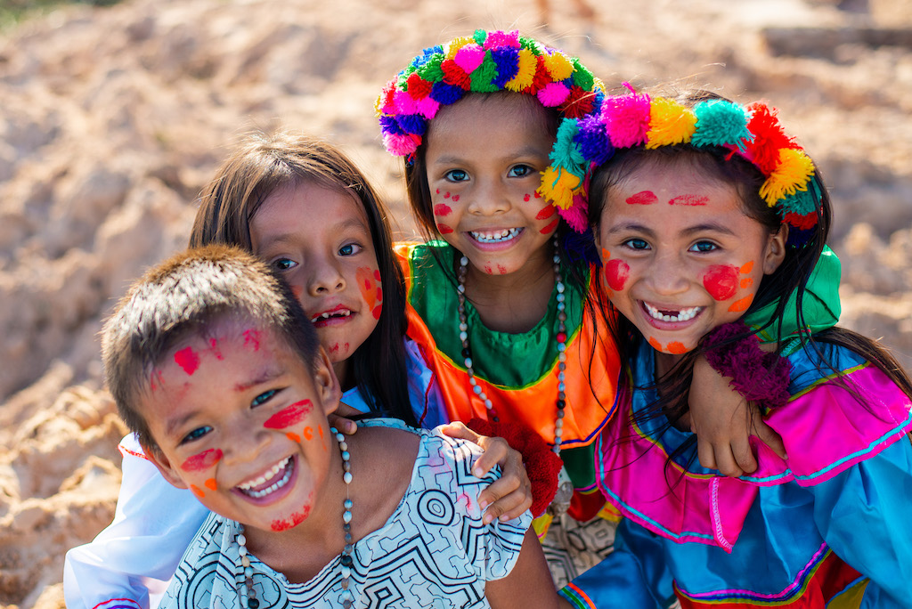 A group of four children in colourful traditional dress.