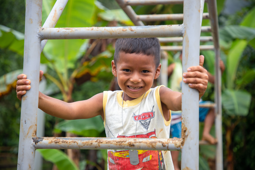 Through a playground ladder, a young boy wearing a white and orange tank top smiles at the camera.