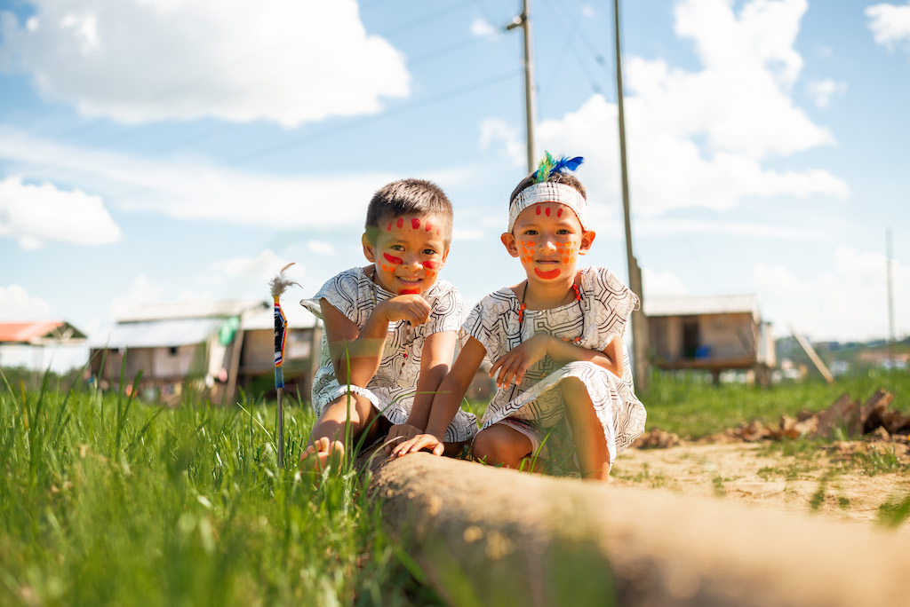 Two boys sit crouched in a field, wearing their tribe's traditional clothing.