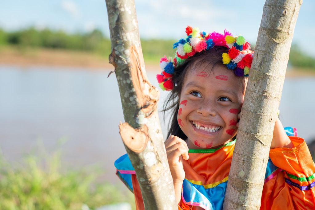 A young Shawi girl wearing a colourful headpeice and dress smiles and looks away from the camera.