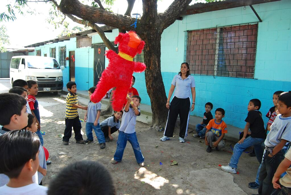 Little boy hits a red pinata surrounded in friends, outside of a blue painted building