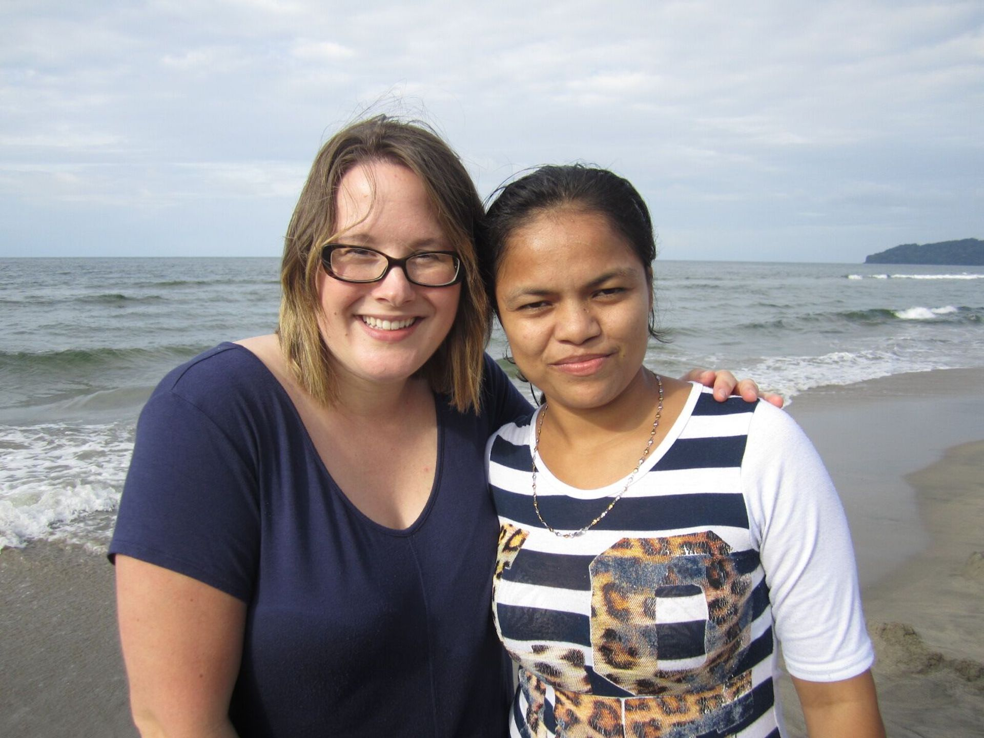 Two women stand together on a beach.