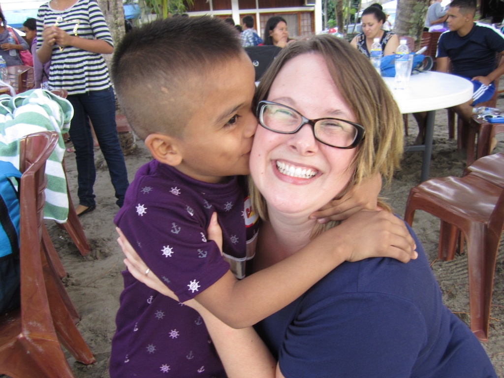 A young boy kisses a smiling woman on the cheek.