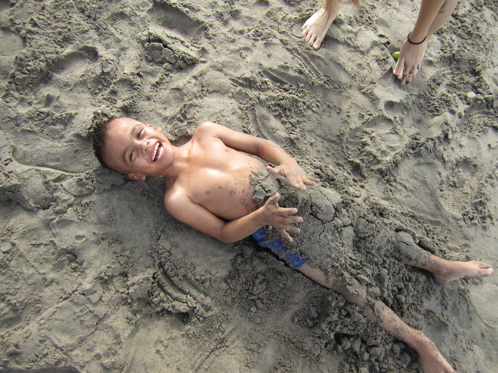 A boy lays on the beach, his legs buried in sand.