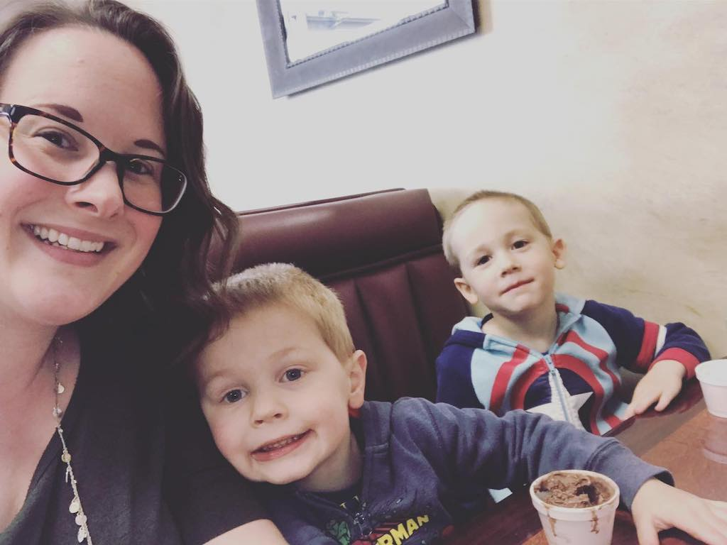 A selfie of a mom with her two sons in a restaurant booth.