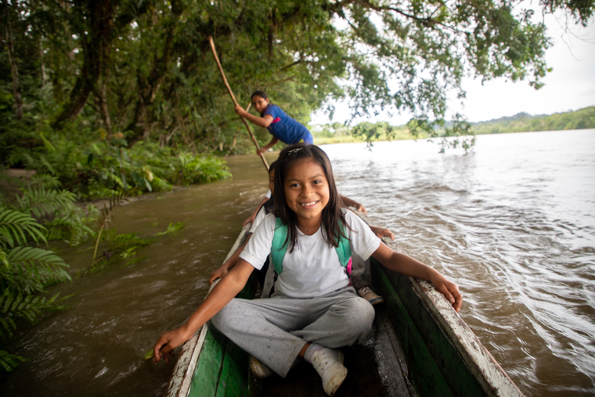 A young girl in a white tshirt sits in a canoe wearing a backpack, on her way to school.