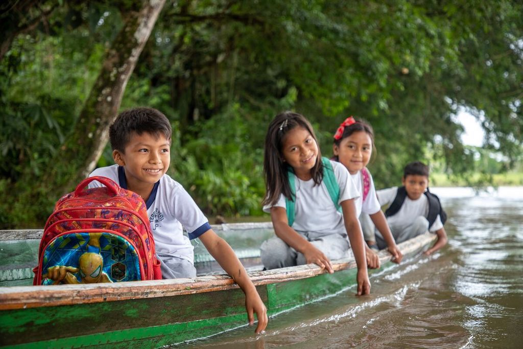 A group of four children sit in a canoe with their backpacks, on their way to school.