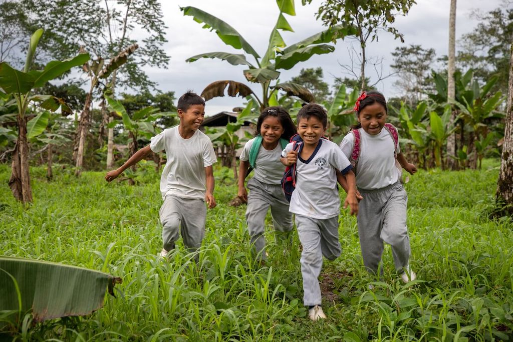 A group of found children run in a field, on their way to school.