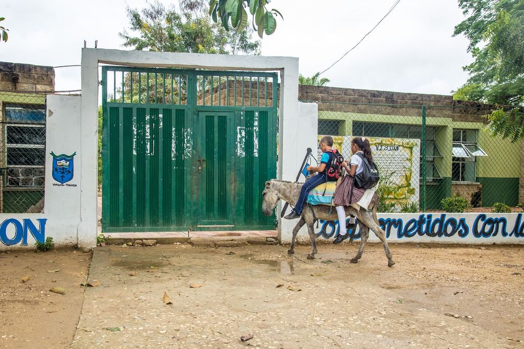 The donkey carrying Dilan and Dianis arrives at the school gate.
