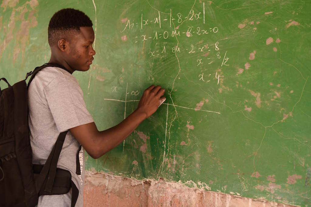 Abdoul writes on a green chalk board.