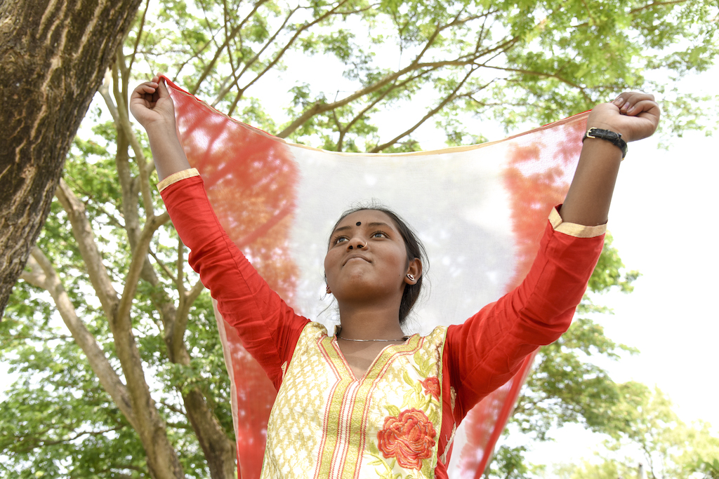 Ratna holds a scarf up behind her head like a banner. She is looking up towards the sky.