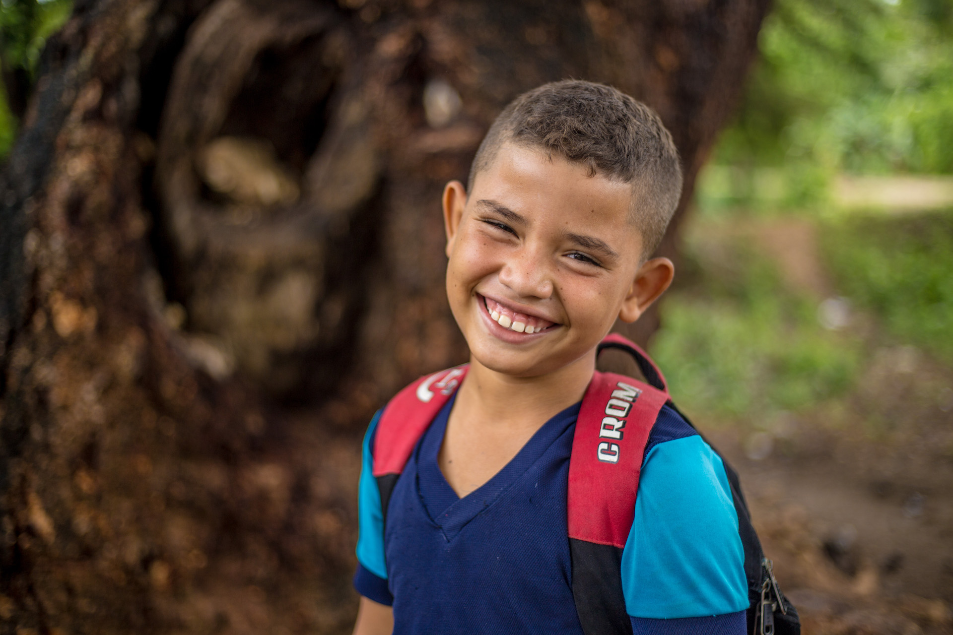 A boy smiles at the camera, wearing a backpack.