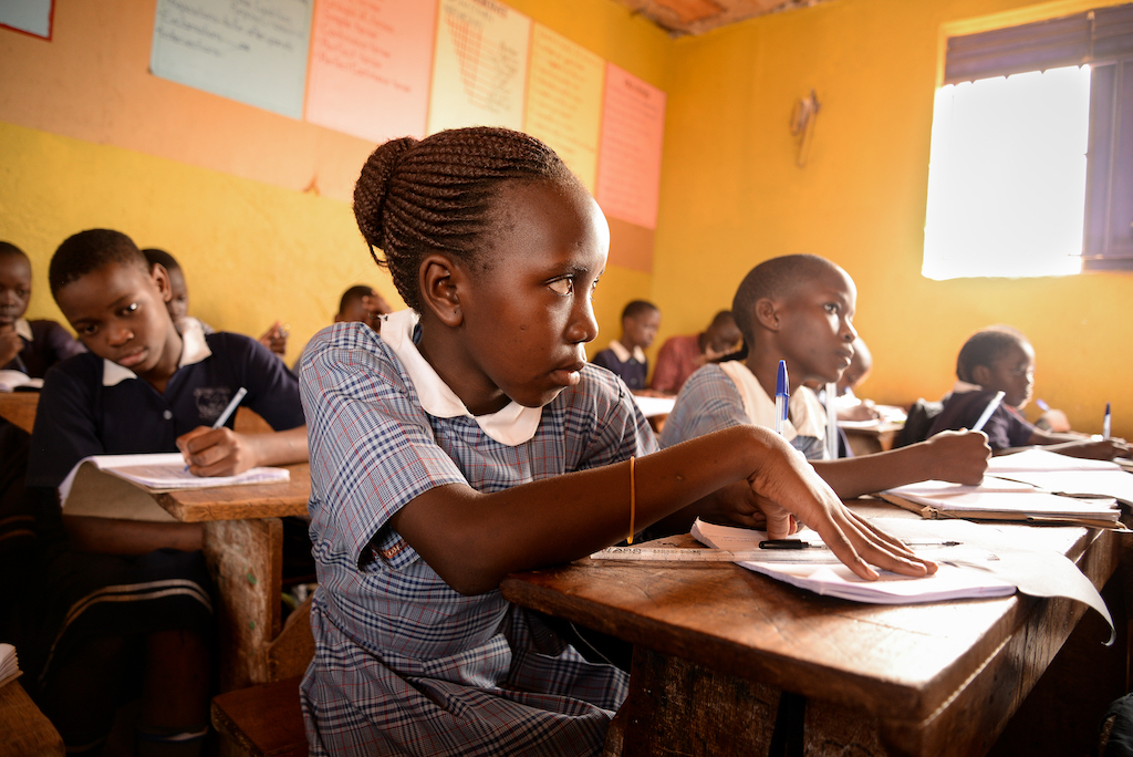 A girl sits at a desk listening to a lesson and writing in a notebook.