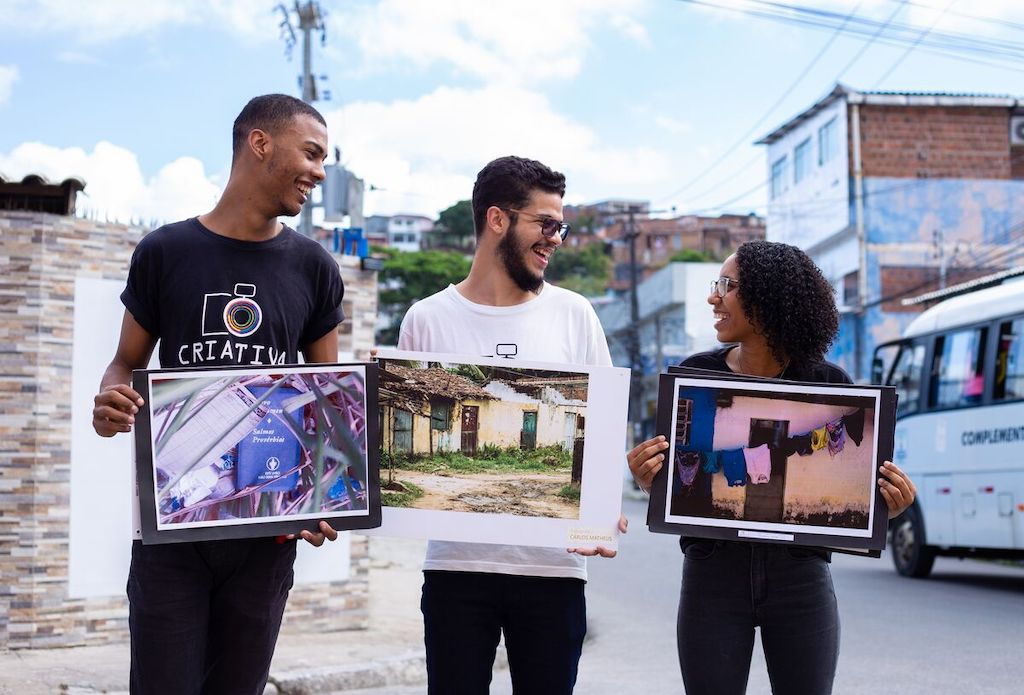 A group of three students pose in a street, each holding a photograph that they took.