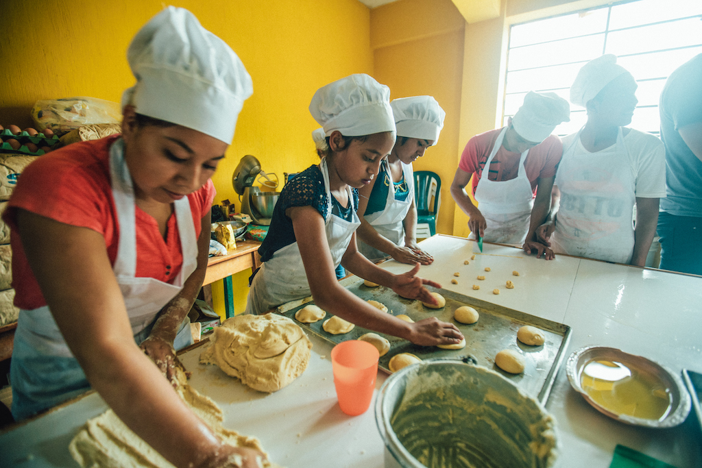 A group of students wearing aprons and chef's hats roll out dough.