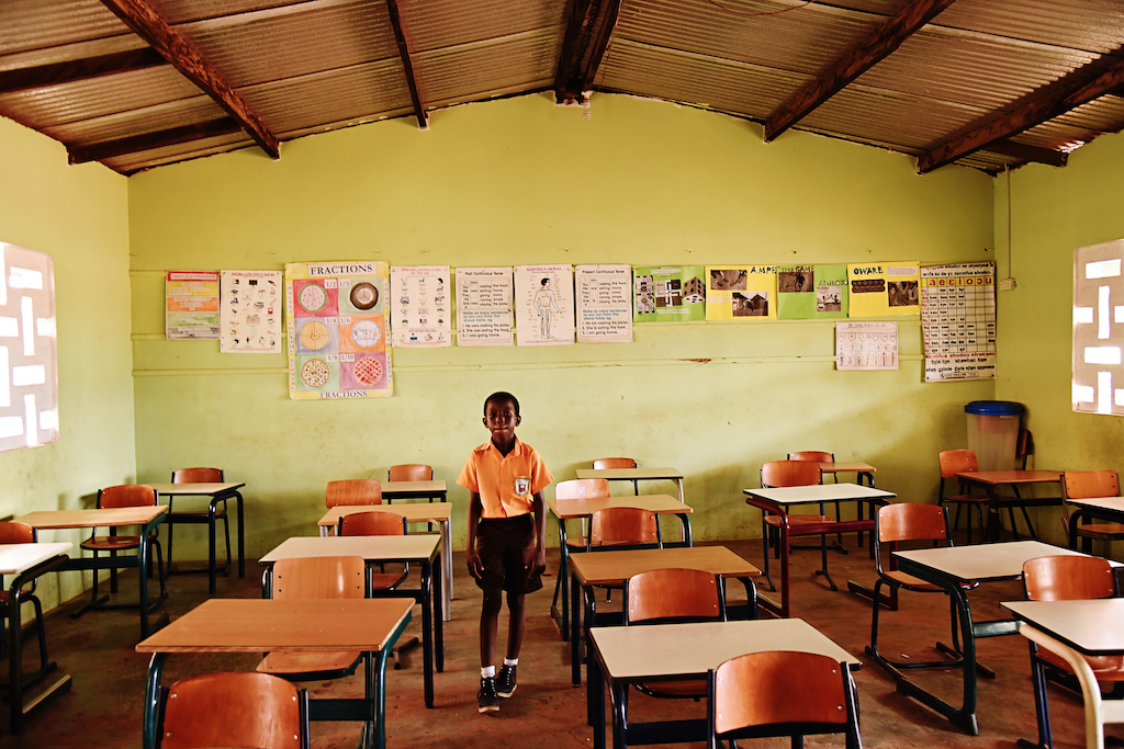 A boy stands amongst desks and chairs in a classroom.