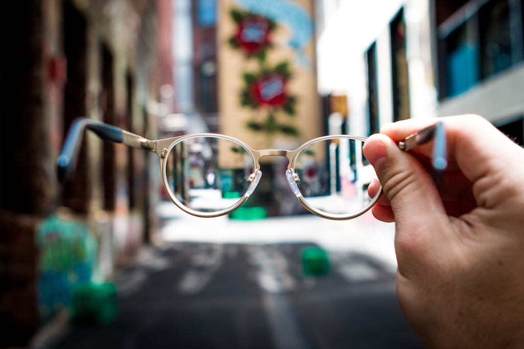 A hand holding out a pair of glasses looking into an alley.