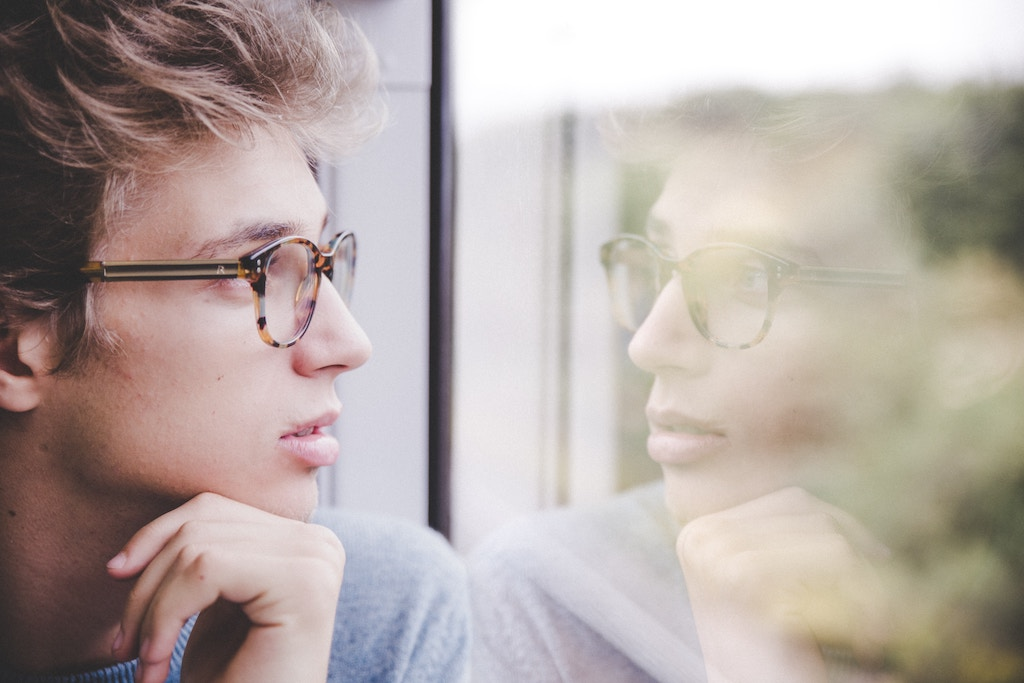 A man wearing glasses looking at his reflection in a window.