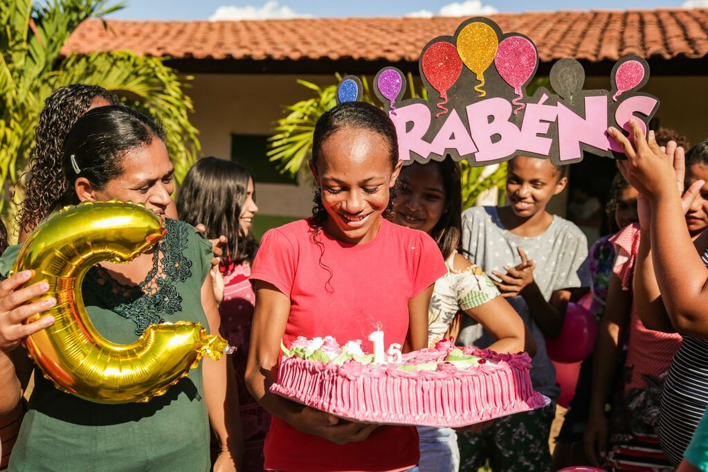 A girl wearing a pink shirt holds a large pink birthday cake. Beside and behind her are balloons.