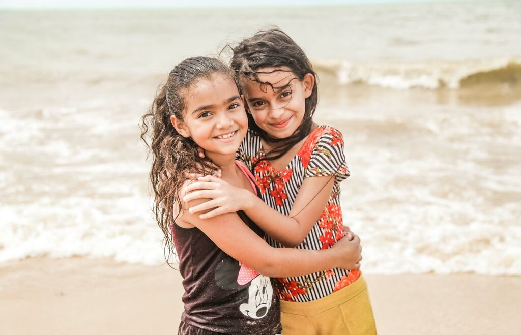 Two little girls hug while looking at the camera, standing in front of the ocean.