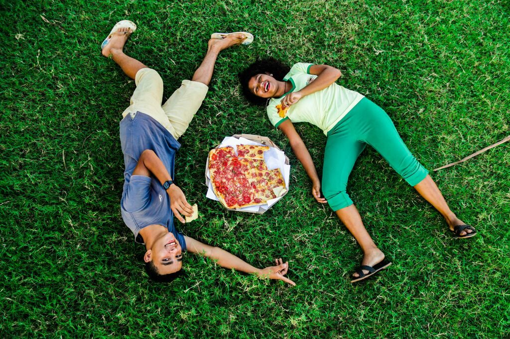 A boy and a girl lie in the grass around a pepperoni pizza.
