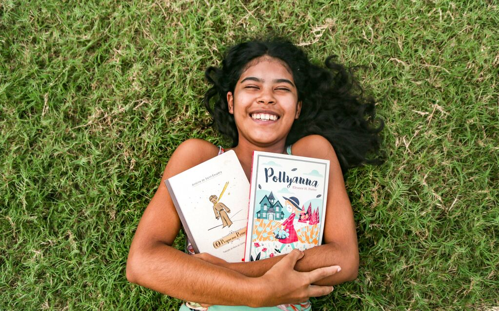 A young teen girl lies in the grass holding two books