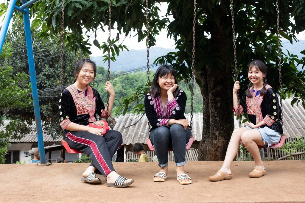 three girls sit on a swing smiling at the camera