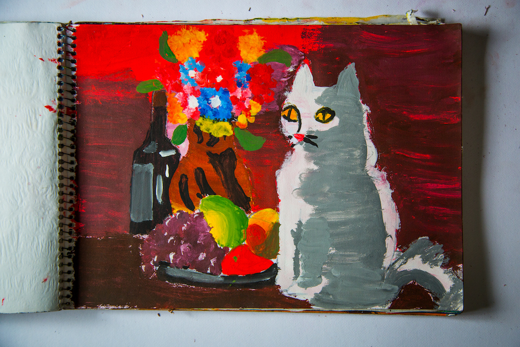 One of Hector's paintings, of a white cat sitting next of a vase of flowers.