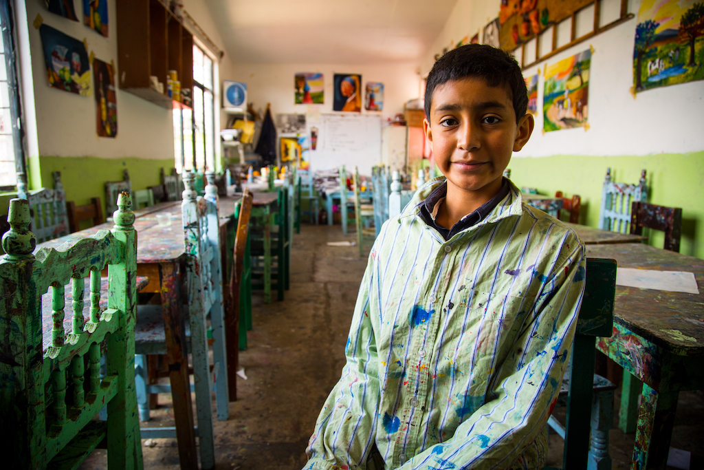 A portrait of Hector sitting in his classroom, wearing his paint smock.