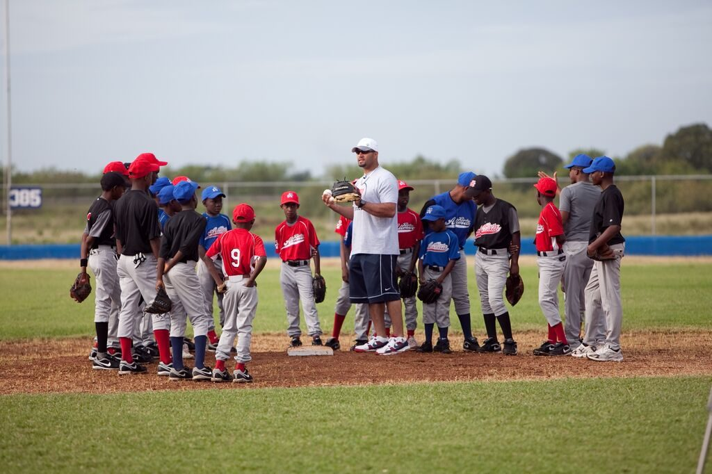 Albert standing in the field with young baseball players