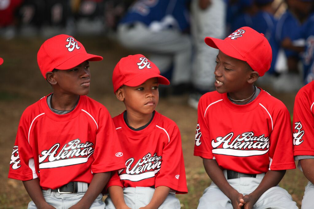 Three kids wearing a red uniform wait at the sidelines