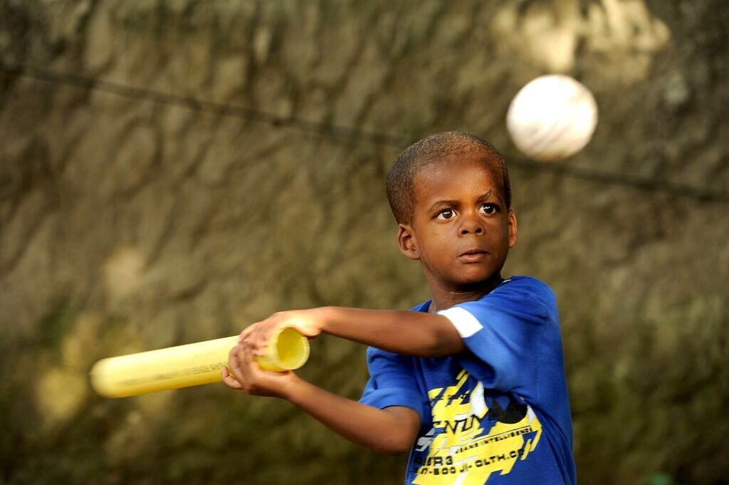 Little Oliver is wearing a blue shirt, trying to hit a white ball with a make-shift bat.