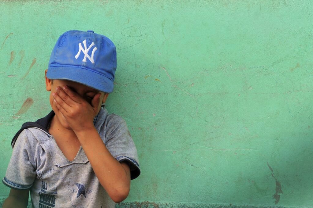 A little boy wearing a Yankees cap laughs and covers his eyes against a turqouise wall