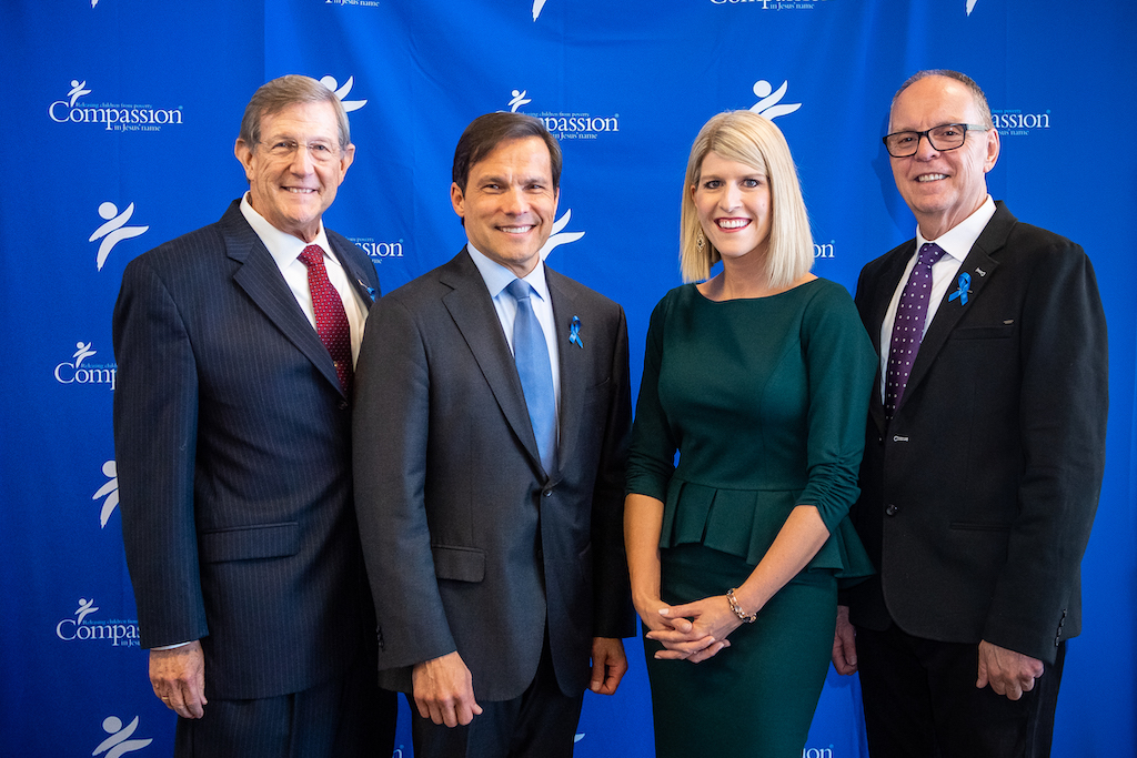 """Dr. Wess Stafford, Santiago """"Jimmy"""" Mellado, Allison Alley and Barry Slauenwhite pose in front of a blue Compassion backdrop."""