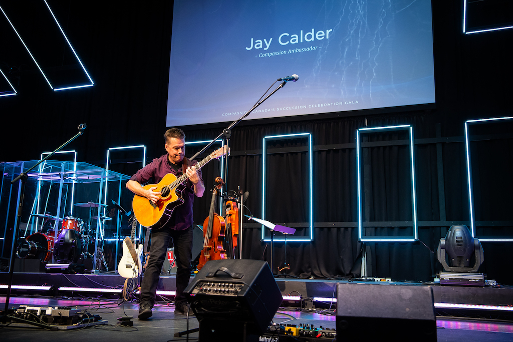 Jay Calder plays guitar on stage.