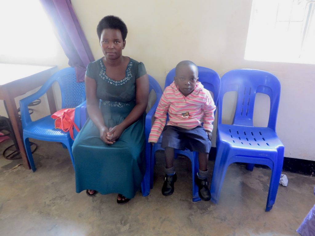 Saviour and his mom wait in his Compassion centre. They sit on blue chairs.