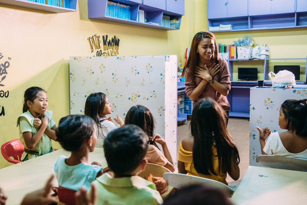 A young woman teaching a class of young children.